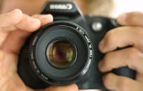 Imagen de unas manos ajustando el objetivo de una cámara de fotos