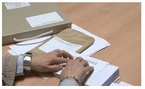En la imagen se puede ver: dos manos leyendo en braille el voto.