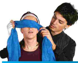 Un chico pasa una venda o pañuelo sobre los ojos de una cica joven