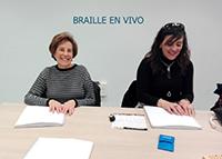 Dos alumnas del taller leyendo un libro en braille.