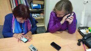 Dos mujeres aprendiendo a usas aplicaciones de móvil